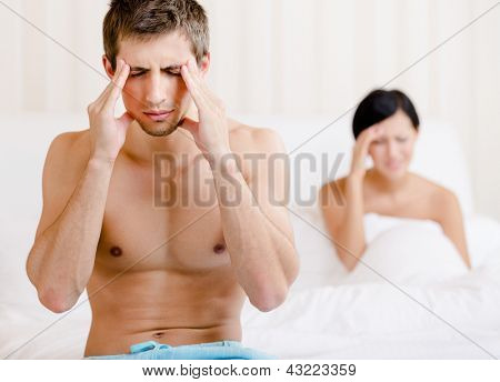 Young couple argues in bed. Depressed man sitting on the edge of the bed. Focus on man