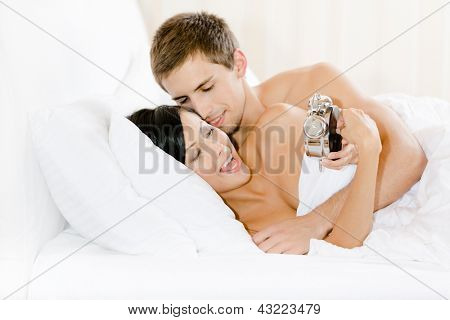 Lying in bed-room with white linen woman shows silver alarm clock to man