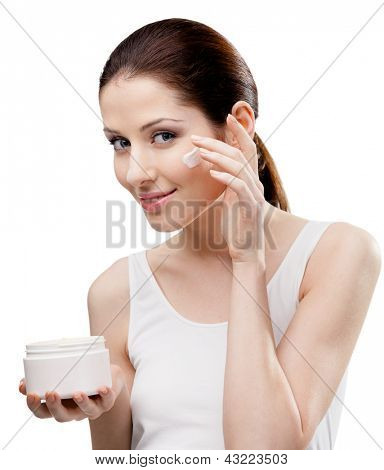 Woman putting on cream from container on face, isolated on white. The pursuit of beauty