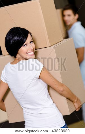 Back view of woman carrying cardboard boxes against the husband while moving to new house