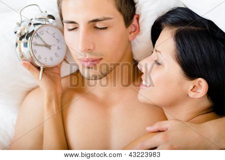 Close up view of couple lying in bedroom. Woman holds alarm clock near the ear of man, top view