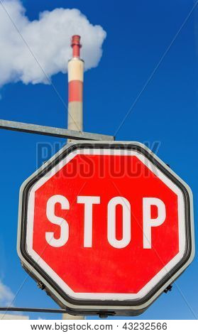 chimney of an industrial enterprise and stop sign. symbolic photo for environmental protection and ozone.