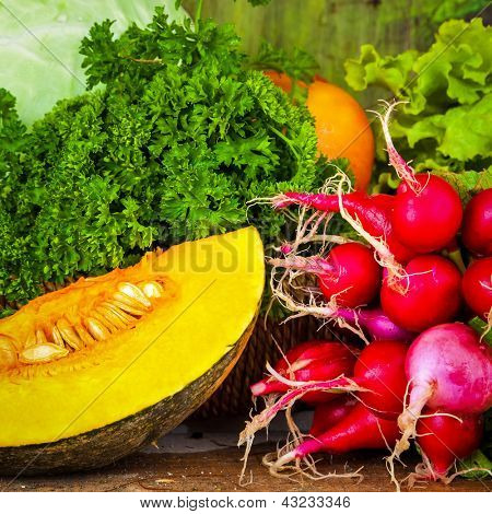 Close up of various fresh and colorful vegetables over wood useful to illustrate healthy or vegetarian food