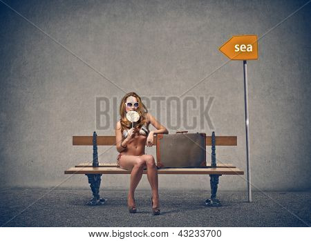 young blonde girl with bikini sitting on the bench