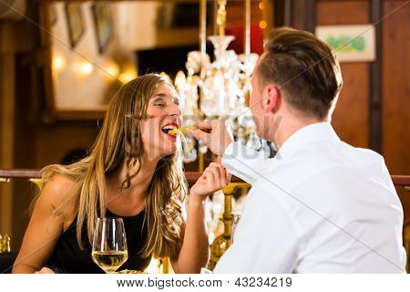 Couple - man and woman - in a fine dining restaurant they eat fast food and fries - a large chandelier is in Background