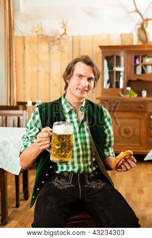 Young man in traditional Bavarian Tracht in restaurant or pub with beer and steins and pretzel