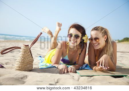 two female friends having fun on the beach