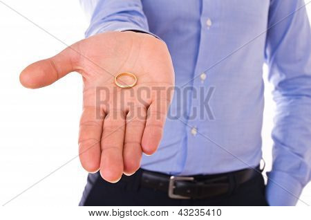 Young man holding gold wedding ring.