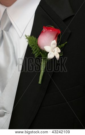 groom with red and white rose boutonniere