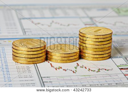 Financial Settlement With The Charts And Golden Coins. Selective Focus
