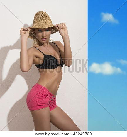 Pretty Girl With Staw Hat, Bra And Shorts Touches The Hat
