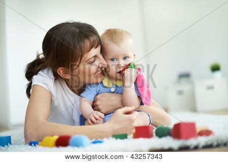 Portrait of happy woman embracing her small son during play