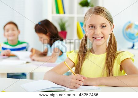 Portrait of lovely girl looking at camera at workplace with schoolmates on background