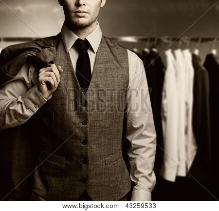 Businessman in classic vest against row of suits
