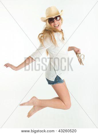 Mujer feliz en pantalones cortos, saltar manteniendo sus zapatos