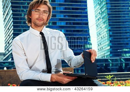 Young business man standing on the street of a big city.