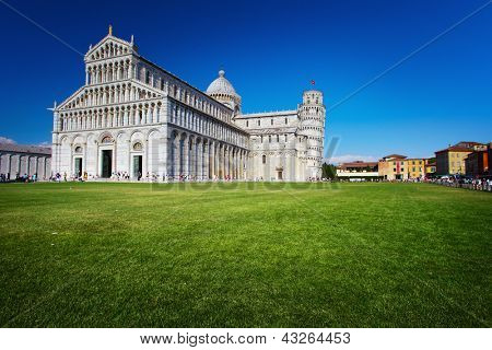 Pisa Cathedral Square with green grass on a meadow and clear blue sky on the background