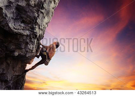 Young man climbing natural rocky wall with sunset sky on the background
