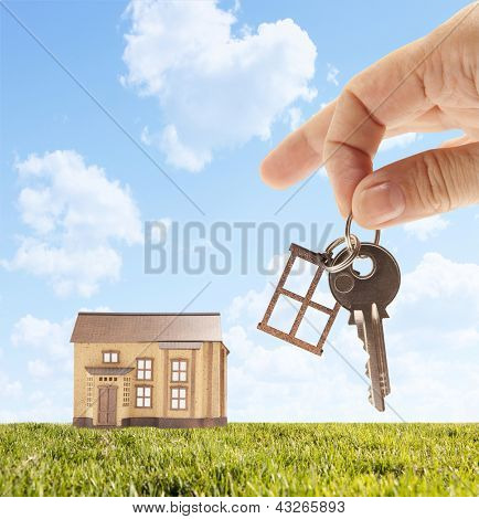 Handing keys in the house sky background