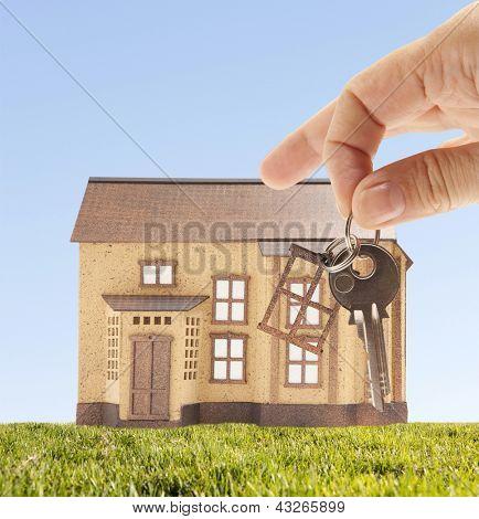 Handing keys in the house sky background