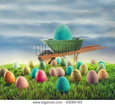 Coloridos huevos de Pascua y la carretilla en la hierba