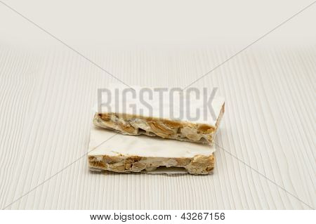 Pieces of Christmas hard almond nougat on white background