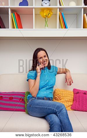 smiley woman sitting on sofa and talking on mobile phone