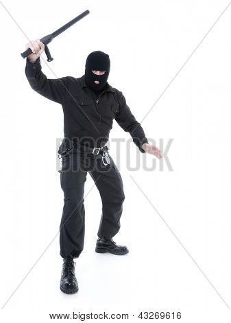 Anti-terrorist police guy wearing black uniform and black mask holding firmly police club in one hand raised in the air ready for action, shot on white