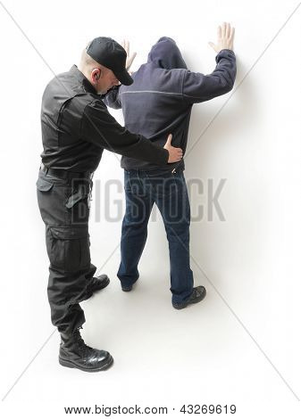 Man being searched by a policeman in black uniform