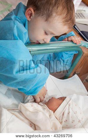 Boy Feeding A Newborn Sister