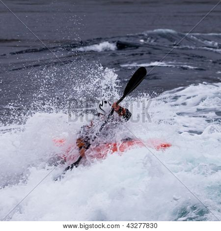 Kayaker in white water paddling breaking waves