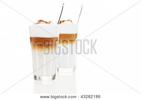 two glasses latte macchiato with chocolate powder and spoons inside