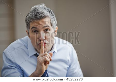 Portrait Of A Businessman With His Finger On Lips