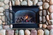 picture of metal grate  - A black metal framed gas fireplace set in colorful river rocks with blue and orange flames in a cabin in Idaho - JPG