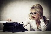 stock photo of crazy face  - blonde journalist with typewriter - JPG