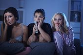 stock photo of pyjama  - Female friends watching horror movie at home in pyjamas at night - JPG