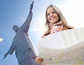 Happy woman traveling to Rio de Janeiro and holding a map