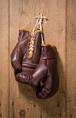 stock photo of boxing gloves  - Boxing Gloves hanging against an old wood wall - JPG