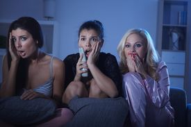 picture of nighties  - Female friends watching horror movie at home in pyjamas at night - JPG