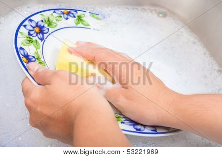 Hands washing the dishes on soapy water
