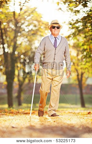Full length portrait of a blind mature person holding a stick and walking in a park