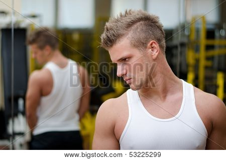 Young Man In Gym Resting And Looking Down To A Side
