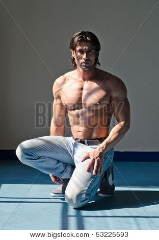 Attractive Muscleman Kneeling Shirtless On Grey Background