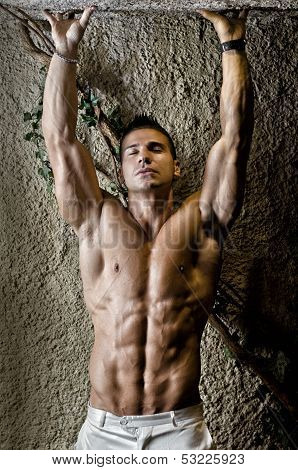 Attractive Muscleman Against Rough Wall, Arms Over His Head