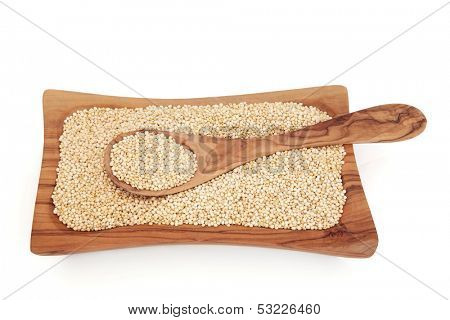 Quinoa super food grain in an olive wood bowl over white background.
