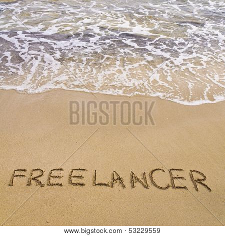 Word Freelancer Written In Sand, On A Beautiful Beach