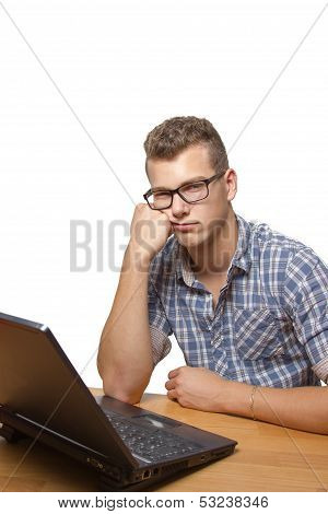 Upset And Bored Boy Sitting In Front Of His Laptop
