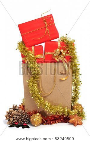 some christmas gifts wrapped with red wrapping paper and with a golden ribbon, in a shopping bag, and christmas ornaments on a white background