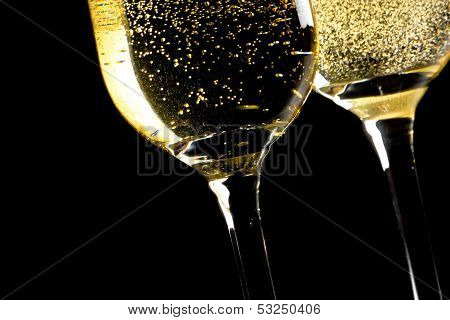 A Pair Of Flutes Of Champagne Tilted With Golden Bubbles