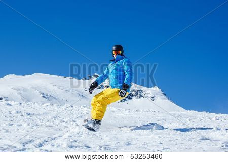 Man on snowboard moving down the hill